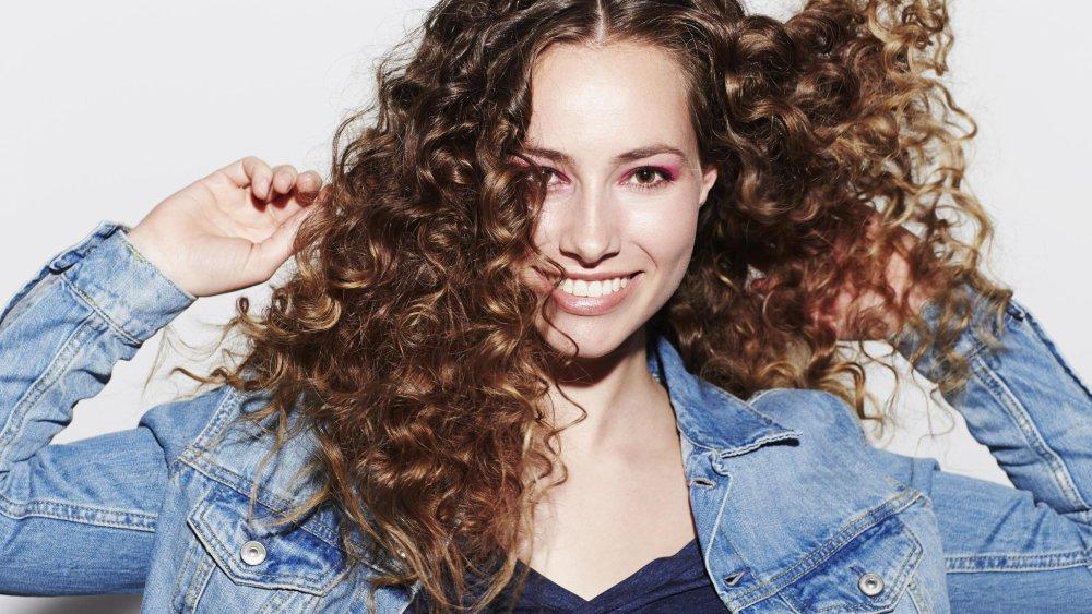femme cheveux bouclés qui sourit